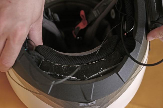 Si dovranno reinserire gli interni del casco, facendo attenzione a nascondere i cavi di collegamento degli auricolari e del microfono.  Dal casco dovrà uscire solo la connessione principale che si aggancia al dispositivo