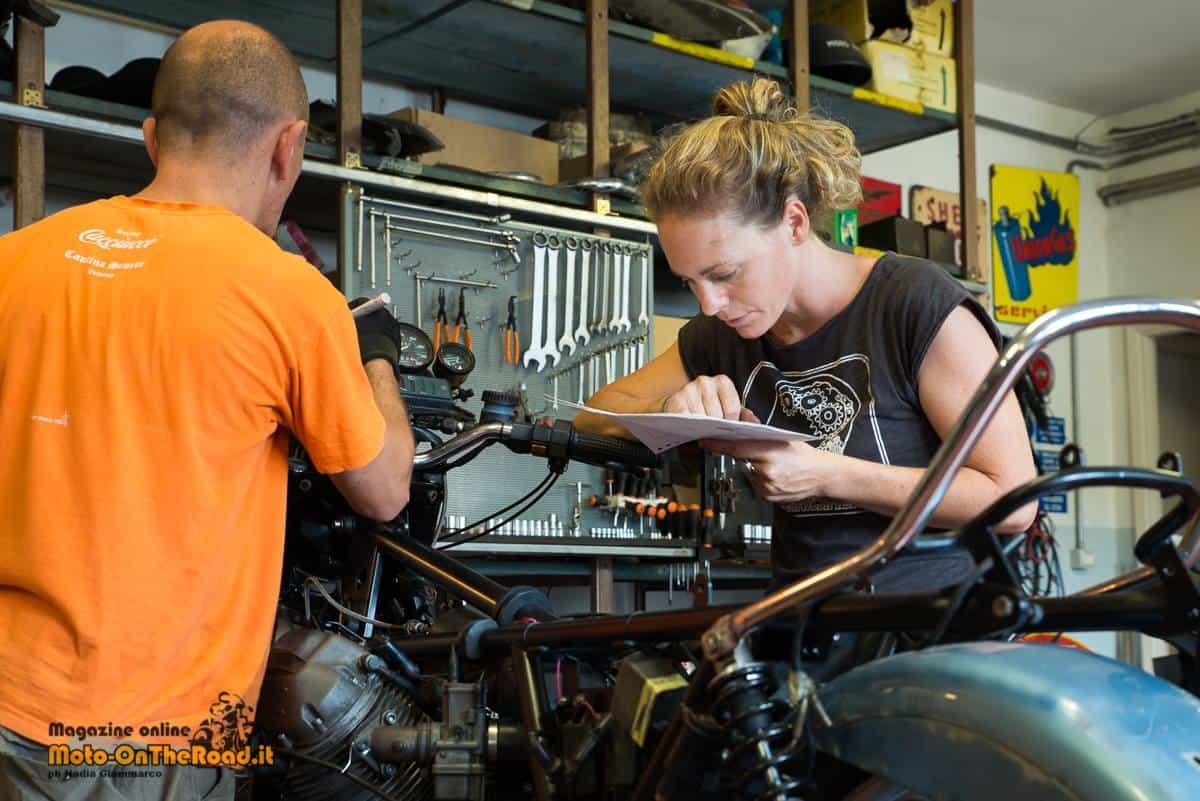 Un cliente alle prese del restauro della sua moto, seguito da Irene.
