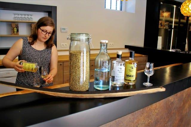 Vallonia in moto: distilleria The Belgian Owl, le materie prime e gli elementi che concorrono alla nascita del whisky: il malto d'orzo, coltivato a filiera corta nei campi intorno alla distilleria, l'acqua della sorgente della proprietà, il distillato (trasparente) che, invecchiato nelle botti usate per il vino, diventa il whisky.