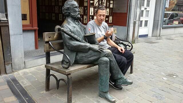 Vallonia in moto: il nostro inviato illustra alla statua di Rudolphe Sax le proprie perplessità in merito all'uso dello strumento.
